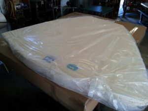 Image of a custom mattress wrapped and ready for shipping.