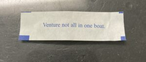 Image of a fortune cookie paper quote 'Venture not all in one boat.'